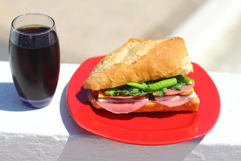 Baguette sandwich cut in half with ham, turkey breast, cheese, lettuce and tomatoes on a cutting Fotografía