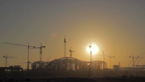 Sunrise appears from behind a silhouette building of the construction site - Tim Footage
