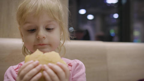 Beautiful happy hungry baby girl eating hamburger. Concept child with fast food Footage