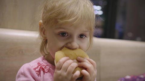 Beautiful happy hungry baby girl eating hamburger. Concept child with fast food Live Action