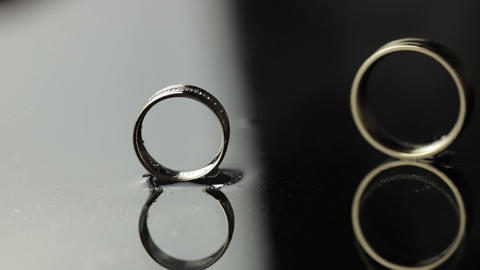 Wedding rings on black, white water surface. Groom ring rolling to bride's ring Live Action
