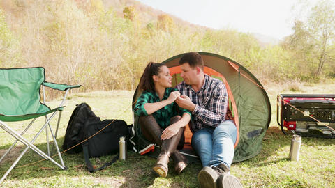 Attractive young couple cuddling in comfortable camping site Footage