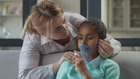 Caring mom supports unwell child in nebulizer mask Footage