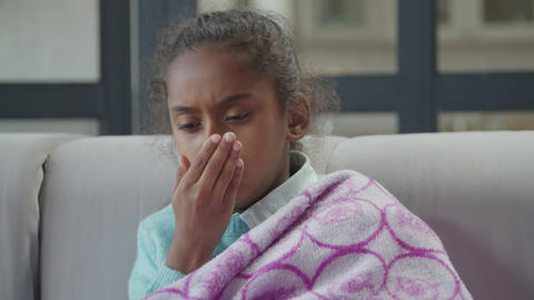 Sick african american girl coughing at home Live Action