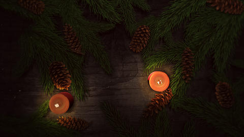 Animated closeup Christmas candle and green tree branches on wood background Animation