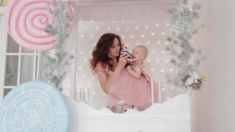Beautiful mother with a one-year-old daughter in beautiful dresses and New Year Live Action