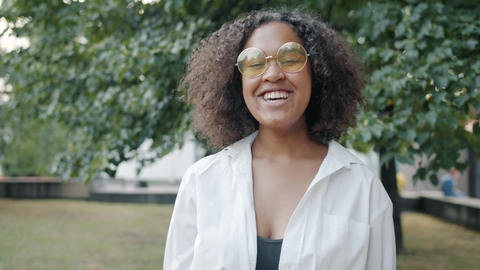 Slow motion of happy Afro-American girl laughing outdoors in urban park Live Action