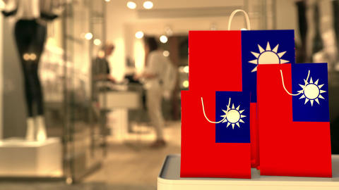 Flag of Taiwan on the paper shopping bags against blurred store entrance. Retail Footage