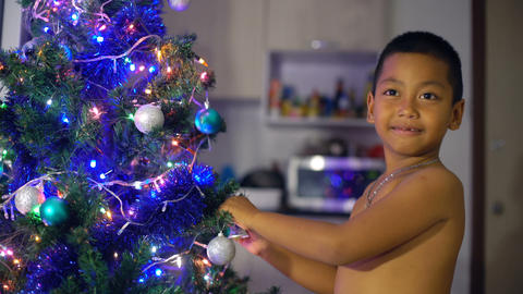 Happy Thai Boy decorates Christmas tree Footage