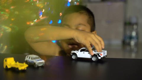 Kid boy playing with toy cars in living room Footage