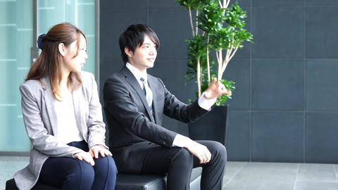 Men and women to talk in the lobby (business colleagues) ビデオ