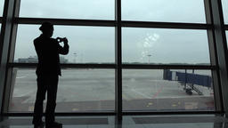 Passenger make photo through terminal window, empty apron and airfield outside Footage