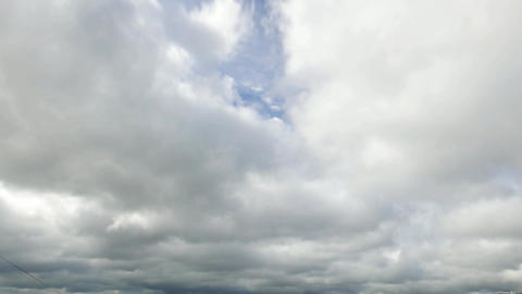 Puffy cumulus clouds quickly rush away, reveal upper strata levels, time lapse Footage