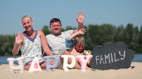 Happy family sitting on the beach and waving hello Footage