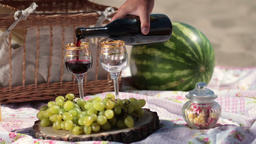 Red wine pouring in crystal glasses on picnic Footage