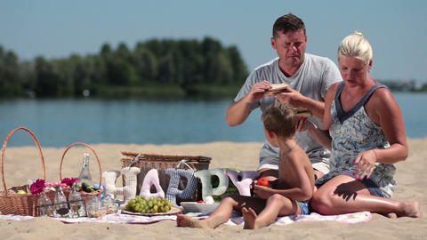 Family with child enjoying picnic on river bank Footage