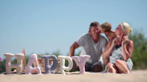 Blurred background of family having rest on beach Footage