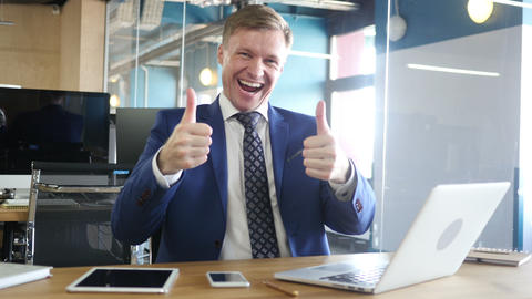 Happy bussinessman giving thumbs up to camera in his office Footage