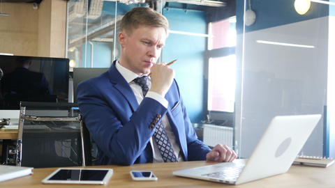 Thinking businessman looking at laptop in his office Footage