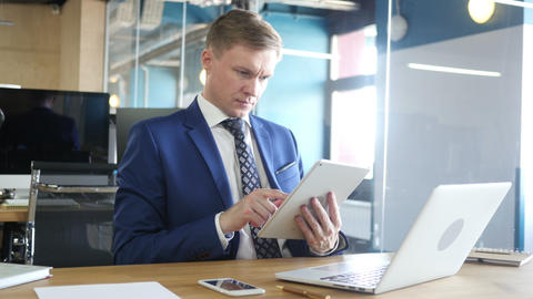 Young businessman using tablet computer while sitting by desk in office Footage