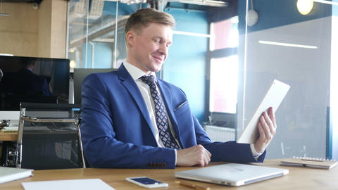 Businessman chatting on tablet computer in the office Live Action
