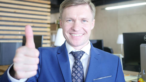 Businessman showing OK sign with his thumb up. Selective focus on face Footage