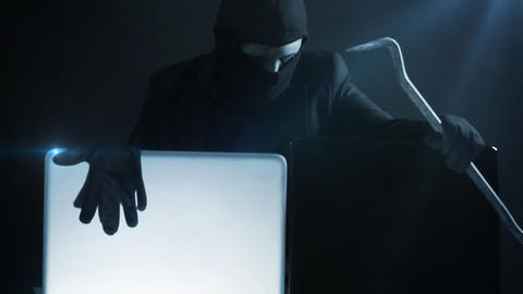 computer hacker in suit stealing data from laptop with crowbar Footage