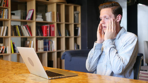 stressed businessman sitting in his office using laptop Footage