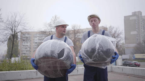 Two adult Caucasian movers walking with packages and talking. Men in white Live Action