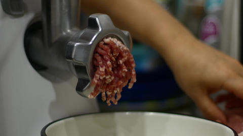 Cooking minced meat in a meat grinder. The meat comes out through many holes Live Action