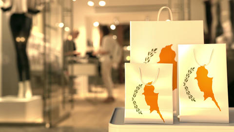 Flag of Cyprus on the paper shopping bags against blurred store entrance. Retail Footage