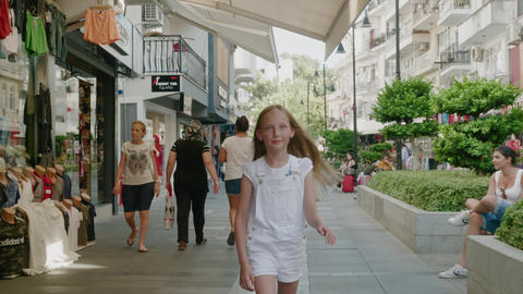 Antalya, Turkey - October 30, 2019: happy girl walking on shopping street in Live Action