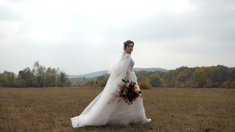 Gorgeous cheerful bride with wedding bouquet walks in Slow Motion along Live Action