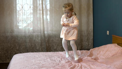Little girl jumping on the bed. A child in a skirt smiles and laughs. Slow Live Action