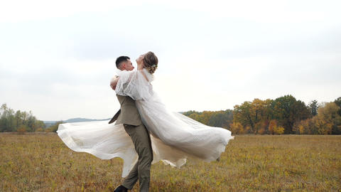 Young Groom spins attractive Bride around in the centre of an autumn field Live Action