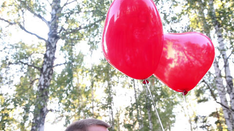 Closeup of a loving couple with helium balloons in form... Stock Video Footage