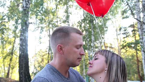 Closeup of a loving couple with helium balloons in form of hearts Footage