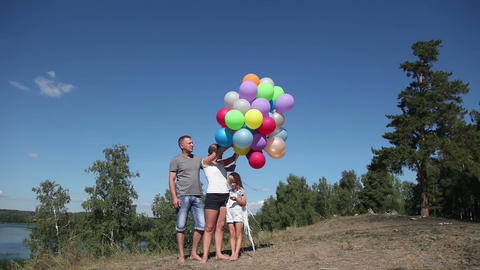 Father, mother and daughter are launching helium balloons into the sky Footage