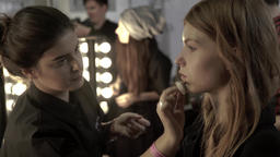 Make-up artist doing make-up girl behind the scenes fashion show Live Action