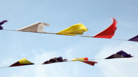 Rope with colorful flags on wind, against blue sky. Small buntings flutter Footage