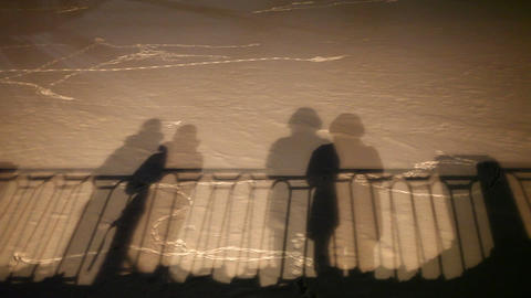 Shadows of moving and static people, hand railing. Ghost image projected on snow Footage