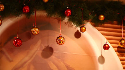 New Year glossy decoration balls hang and sway in air against printed wall-paper Footage