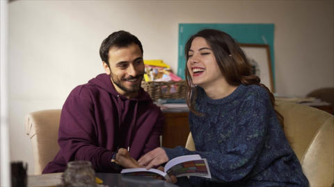Young couple reading a magazine and laughing at cafe - Slow Motion Live Action
