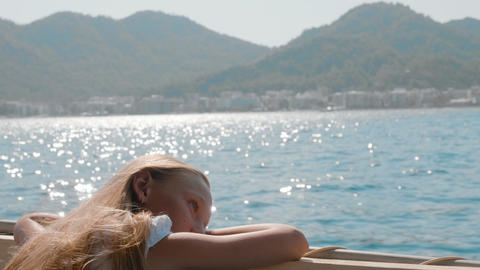 Pensive girl sitting in boat and looking at water during sea trip Live Action