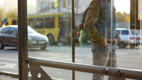 A man is waiting for a bus at a bus stop. He is late, looks at his watch, shifts Live Action