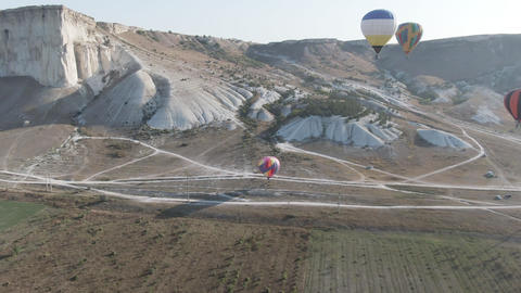 Balloons soar over the Valley amid protruding mountain ranges, the morning sun Footage