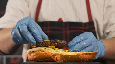 Close-up top view of a cook's hands cooking a hamburger Live Action