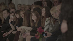 Spectators watch a model during the fashion show Footage