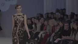 Girl model performs at a fashion show walking down the path in front of the audi Footage