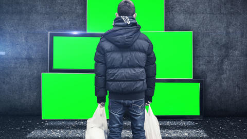 a young boy stays in front of tv screens and looking to the tv green screen Animation
